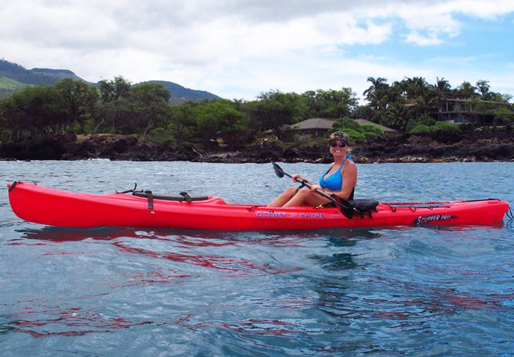 Corrinna wearing a hat and sunglasses is paddling a red single person kayak off of the coast of Makena Maui.