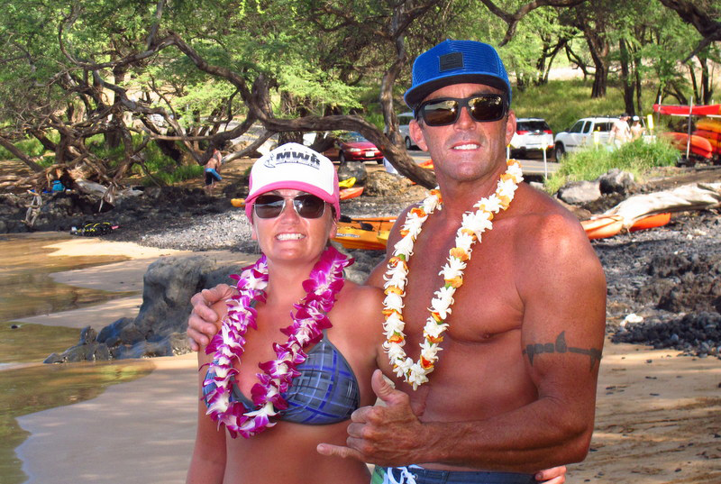 Maui Ocean Rentals owners, Corrinna and Scotty smile and are wearing sunglasses and flower leis at the beach while throwing a shaka.