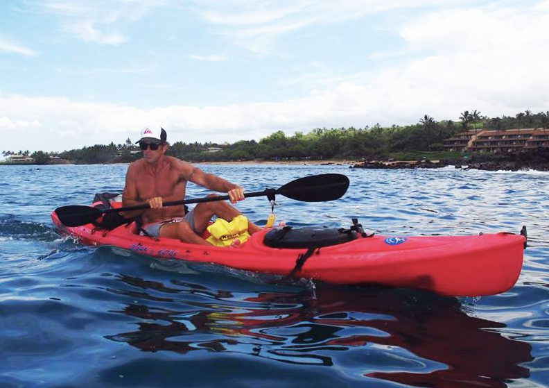 Scotty wearing a hat and sunglasses is paddling a red single person kayak off of the coast of Makena Maui.